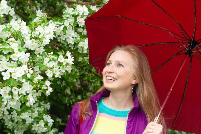 Fille riante sous un parapluie sur le fond d'un pommier de floraison photographie stock libre de droits