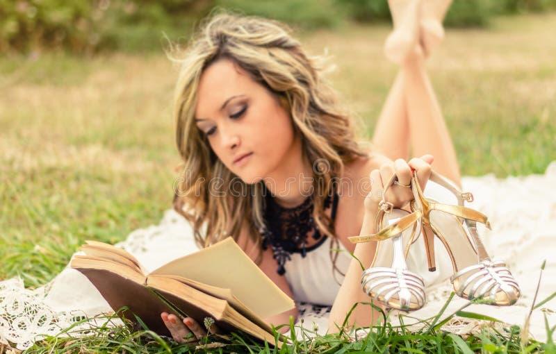 Fille romantique avec des chaussures dans la main a de lecture images libres de droits