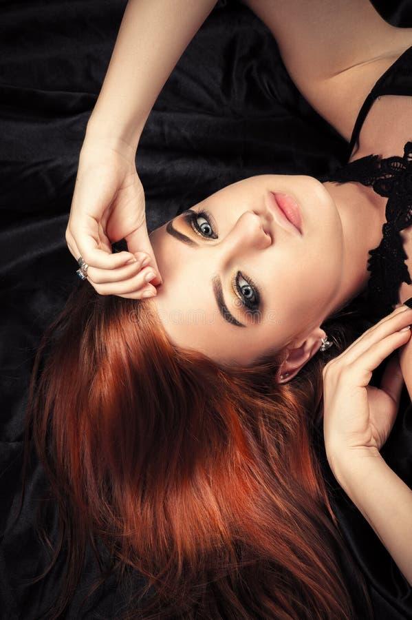 Fille rousse attirante avec le maquillage à la mode se couchant images stock