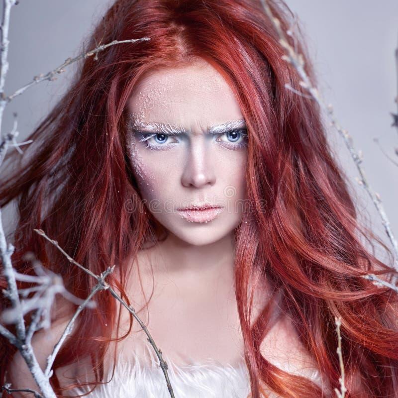 Fille rousse avec de longs cheveux, un visage couvert de neige avec les sourcils blancs de gel et des cils dans le gel, une branc photos stock