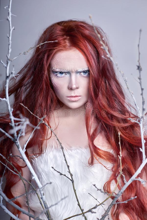 Fille rousse avec de longs cheveux, un visage couvert de neige avec les sourcils blancs de gel et des cils dans le gel, une branc images libres de droits