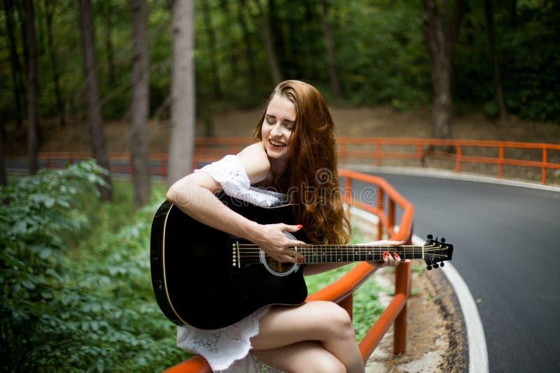 Fille rousse avec une guitare chantant dans un voyage par la route photos libres de droits