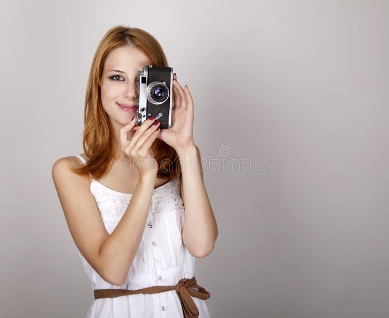 Fille rousse dans la robe blanche avec l'appareil-photo de cru. photo libre de droits