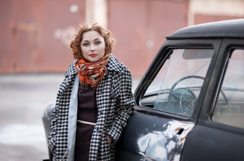 Fille rousse dans le style de vintage près de la vieille voiture images stock