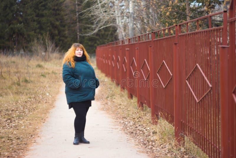 Fille rousse dans une veste verte sur la rue photographie stock libre de droits