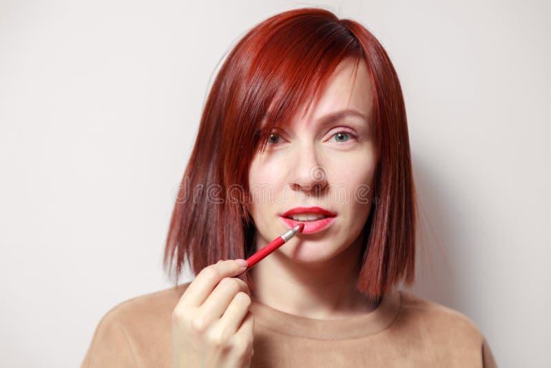 Fille rousse de portrait de plan rapproché la jolie peint ses lèvres avec le rouge à lèvres rouge de crayon L'école de concept du photo libre de droits