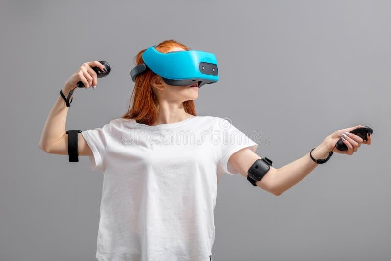 Fille rousse employant des verres de VR au-dessus de blanc Exp?rience de r?alit? virtuelle photos libres de droits