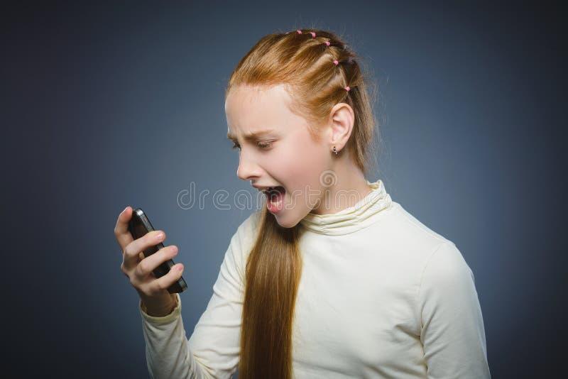 Fille rousse fâchée avec le téléphone portable D'isolement sur le gris images stock