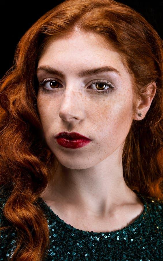 Fille rousse magnifique Jeune belle femme pousse au studio Incline la tête et regarde avec joie Languettes rouges Robe verte Vert photographie stock libre de droits