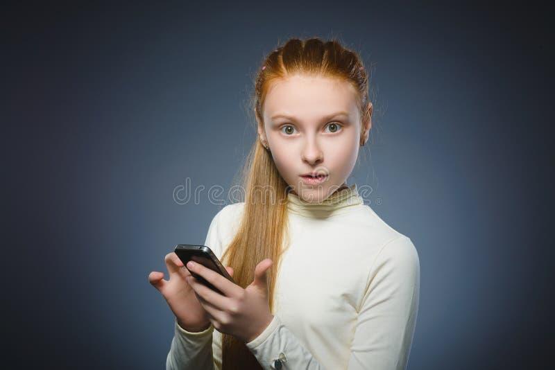 Fille rousse mignonne étonnée avec le téléphone portable D'isolement sur le gris photo stock