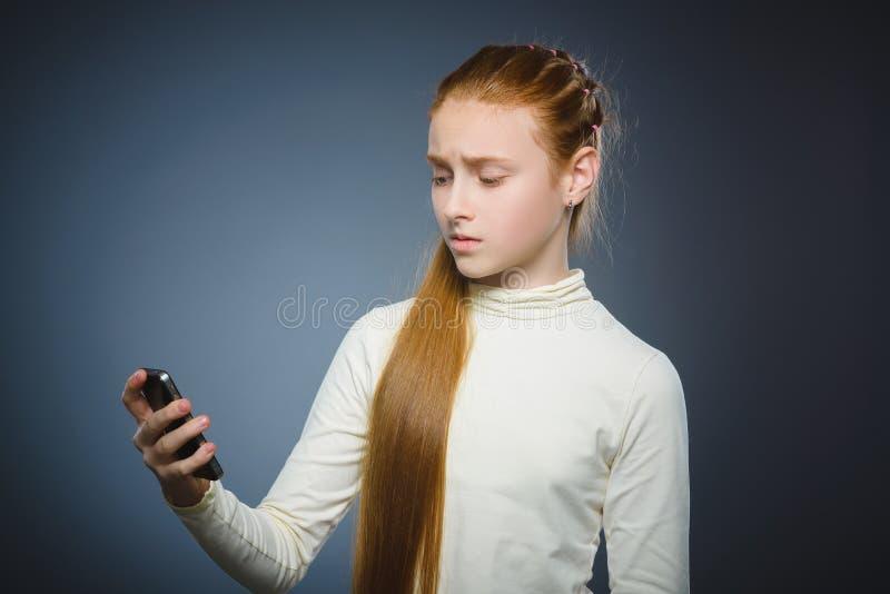 Fille rousse mignonne étonnée avec le téléphone portable D'isolement sur le gris photographie stock