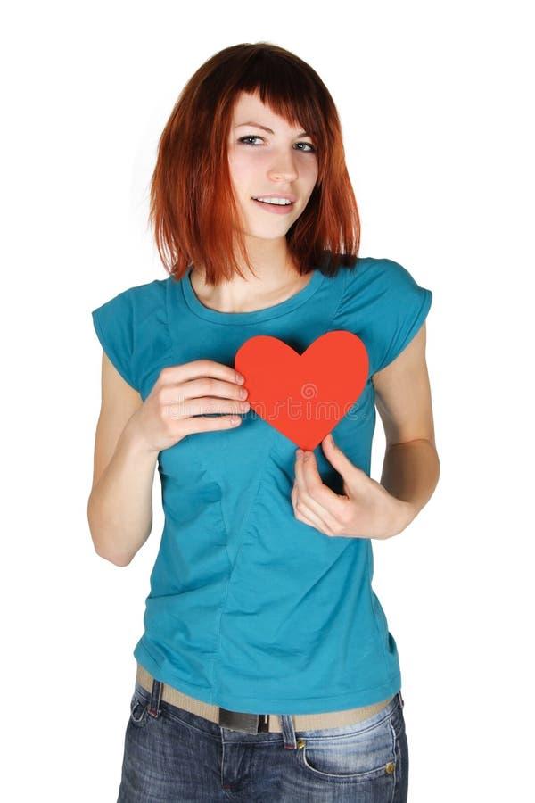 Fille rousse retenant le coeur de papier rouge sur son sein images stock