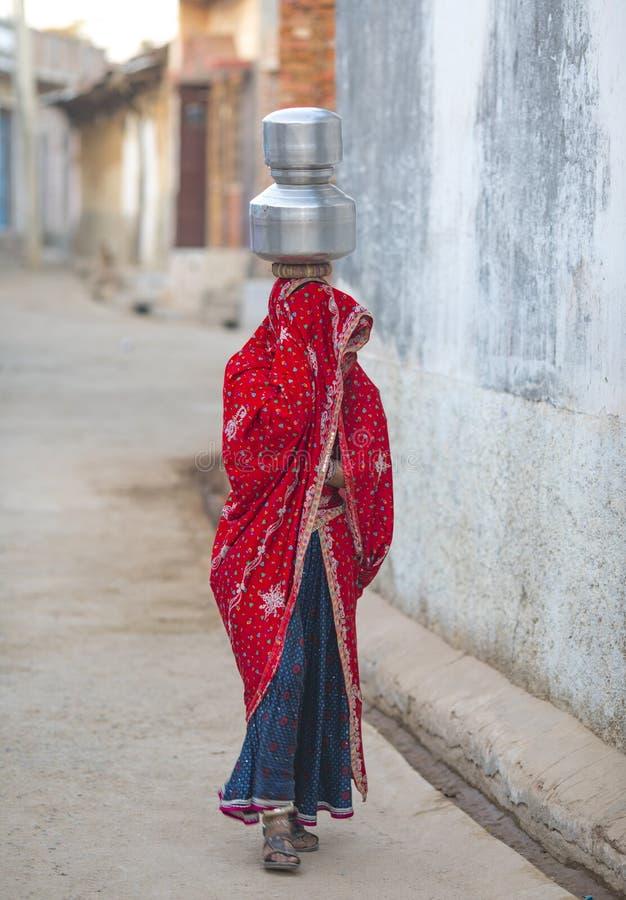 Fille rurale porter l'eau images stock