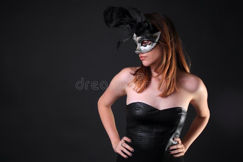 Fille séduisante dans un masque noir de robe et d'argent image stock