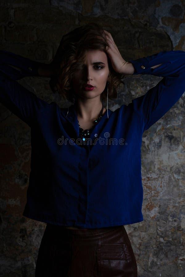 Fille séduisante de brune avec le chemisier de port et le collier de cheveux bouclés posant avec la lumière dramatique image libre de droits