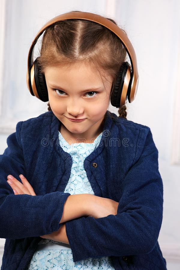 Fille sérieuse drôle fâchée d'enfant dans la veste bleue écoutant la musique image libre de droits