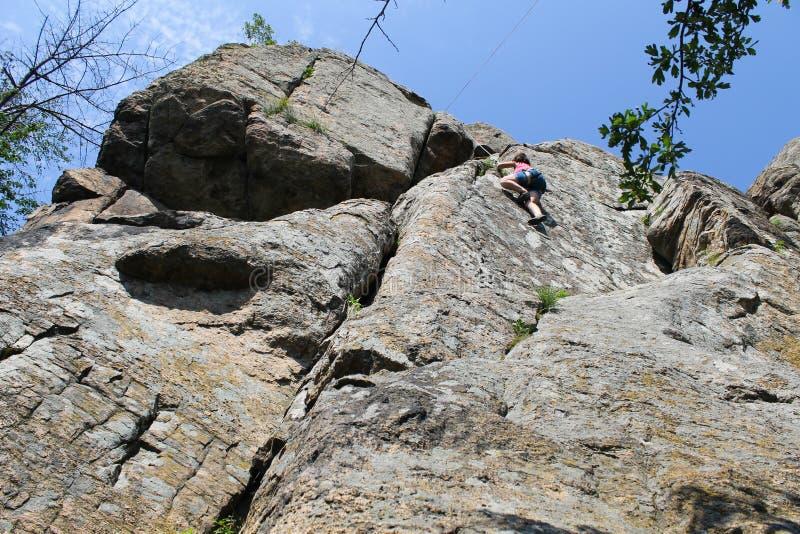 Fille s'élevant sur la roche photo stock