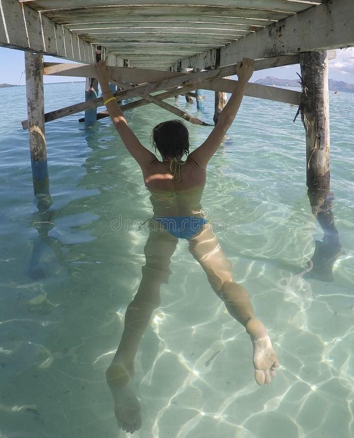 Fille s'étirant sur un pilier en bois dans la plage image stock