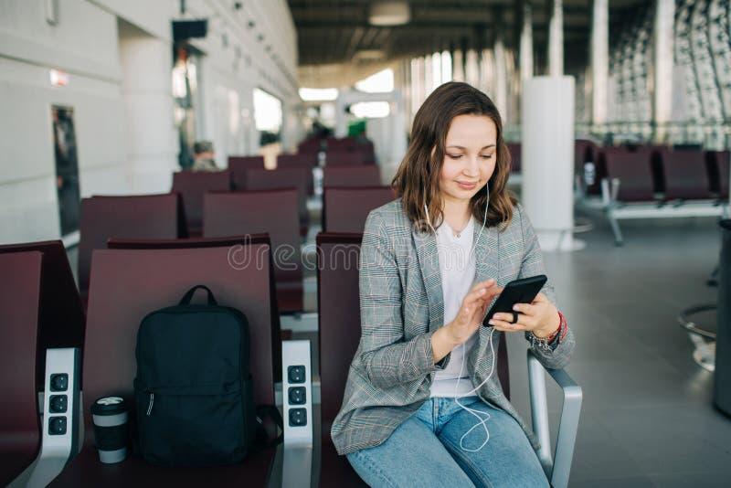 Fille s'asseyant à l'aéroport, mettant en rouleau le smartphone images libres de droits