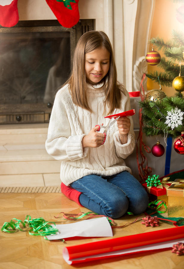 Fille s'asseyant à l'arbre de Noël et coupant des flocons de neige hors de décembre photo libre de droits