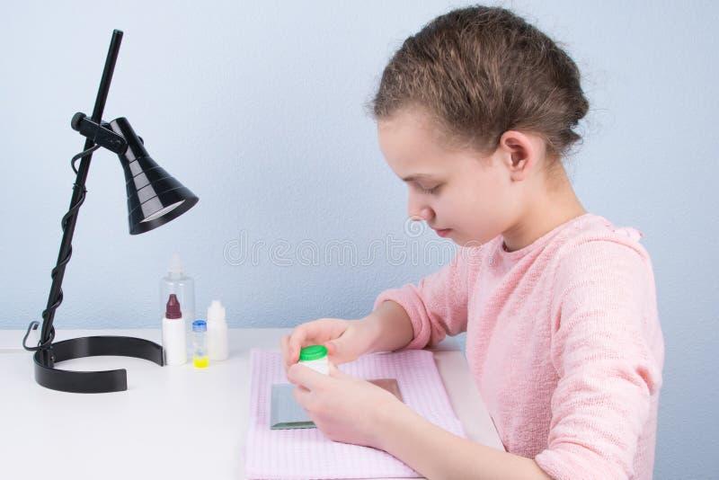 fille s'asseyant à la table et tenant un conteneur pour stocker des verres de contact images libres de droits