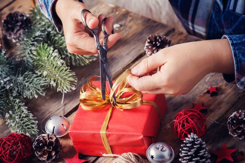 Fille s'asseyant à son bureau attachant l'arc pour le cadeau de Noël Plan rapproché des mains et de la boîte rouge avec le ruban  photographie stock libre de droits