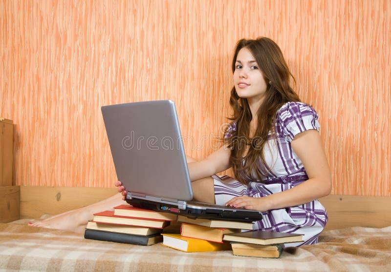 Fille s'asseyant avec l'ordinateur portatif photographie stock libre de droits
