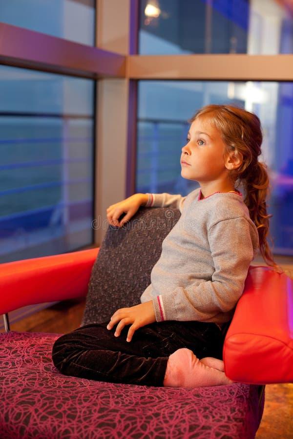Fille s'asseyant dans la présidence dans la cabine dans le bateau photo stock