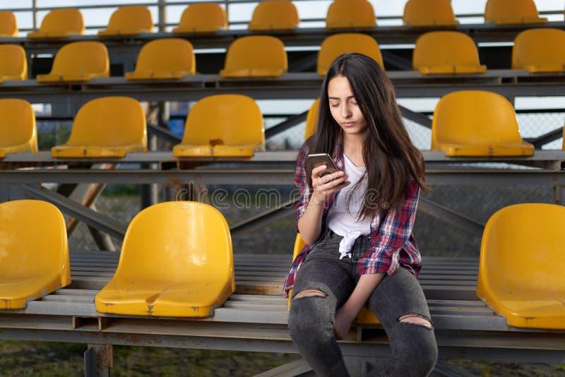 Fille s'asseyant dans les supports et les regards à un téléphone portable photo stock