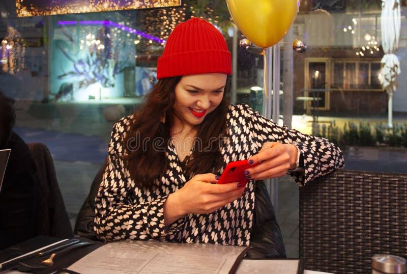 Fille s'asseyant dans un café avec le téléphone portable image stock