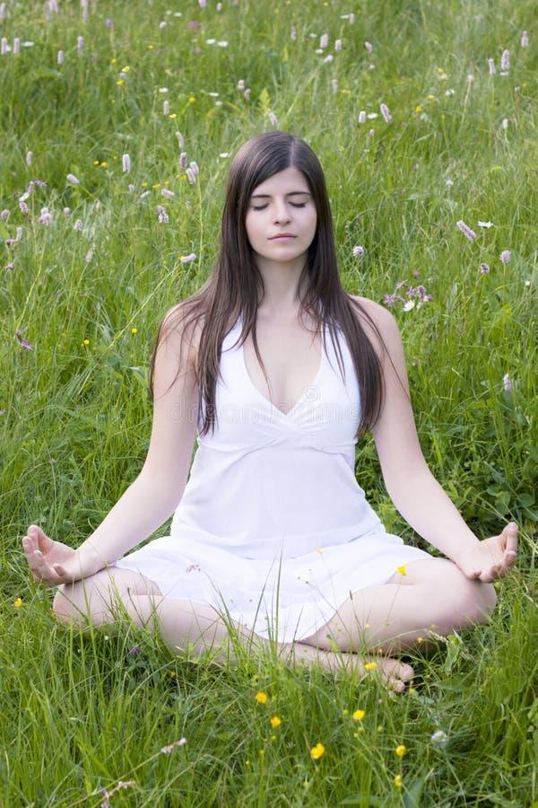 Fille s'asseyant en position de yoga dans le pré photo stock