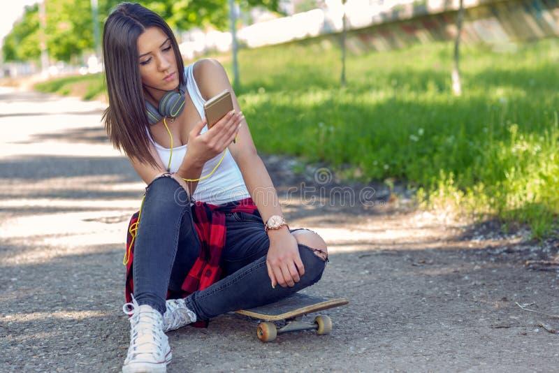 Fille s'asseyant ? la planche ? roulettes et au t?l?phone portable d'utilisation Dehors, mode de vie urbain image stock