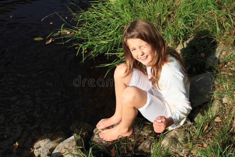Fille s'asseyant par une rivière images stock