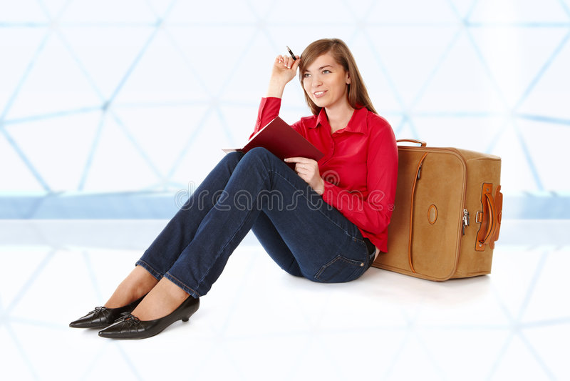 Fille s'asseyant près d'une valise images stock