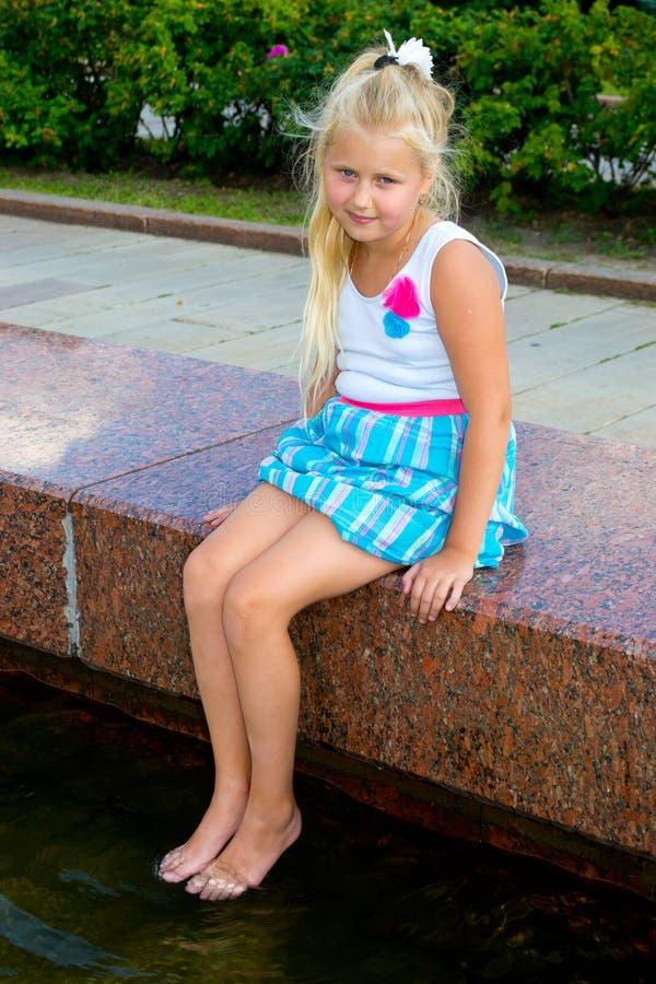 Fille s'asseyant près de l'eau photo stock