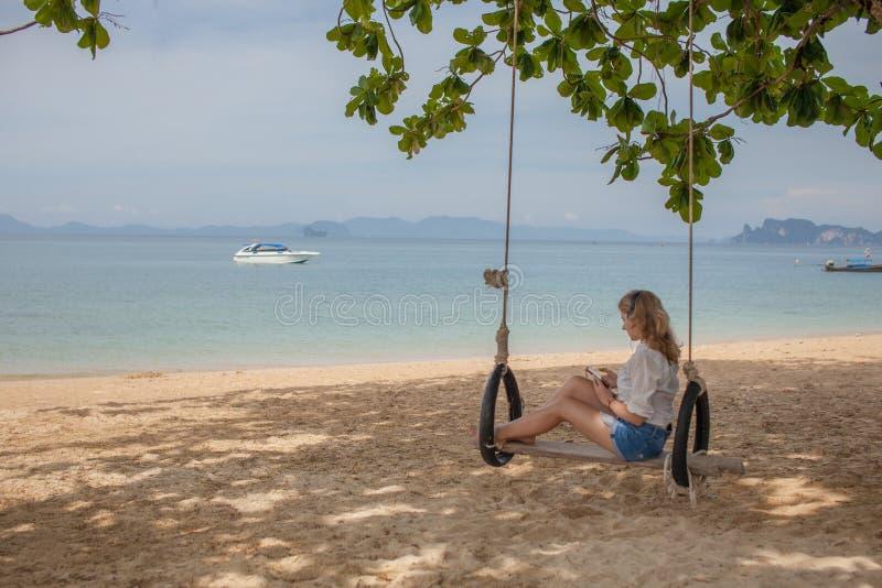 Fille s'asseyant sur l'oscillation sur la plage tropicale photographie stock