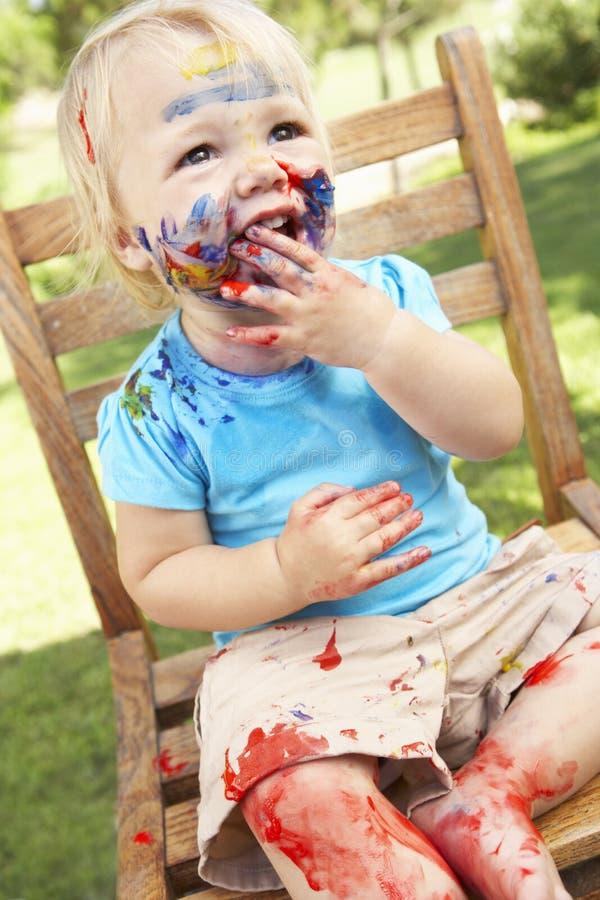 Fille s'asseyant sur la chaise couverte en peinture images stock