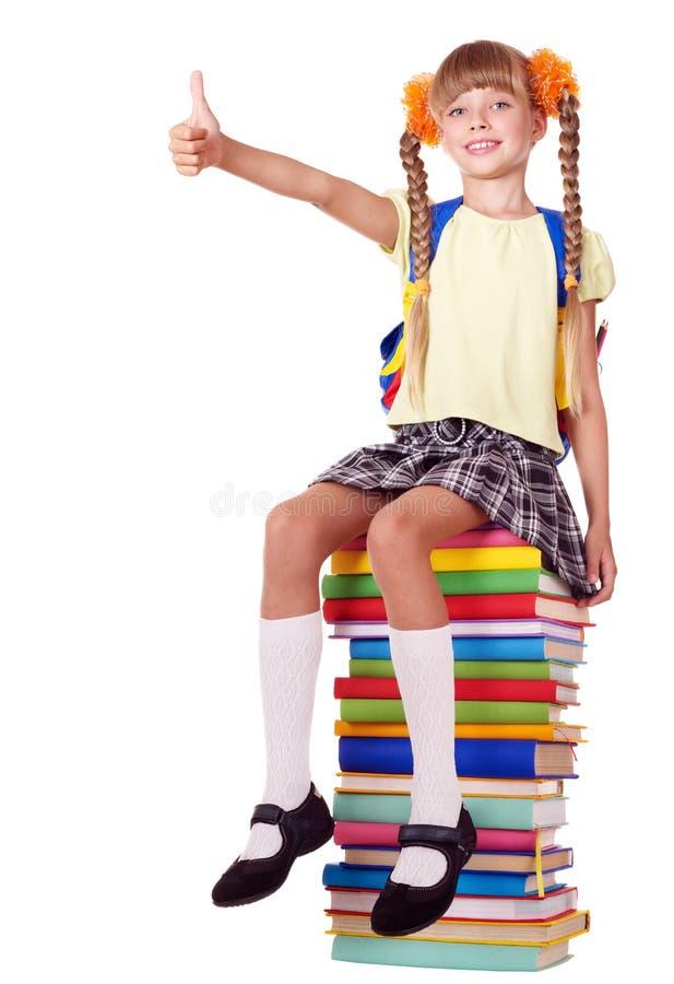Fille s'asseyant sur la pile des livres affichant le pouce vers le haut. photographie stock libre de droits