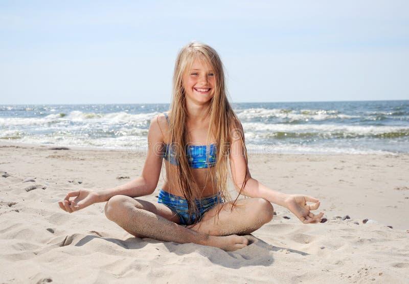 Fille s'asseyant sur la plage image stock