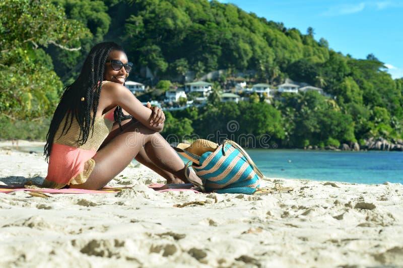 Fille s'asseyant sur la plage photos stock