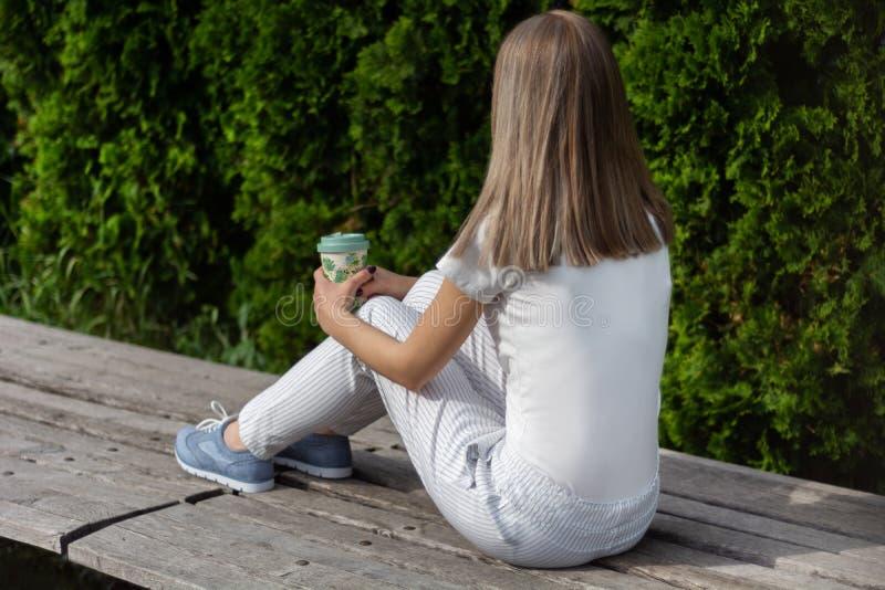 Fille s'asseyant sur le banc avec le pantalon rayé et tenant la tasse de café Fille se reposant en parc sur le temps beau photos libres de droits