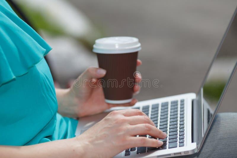 Fille s'asseyant sur le banc et à l'aide de l'ordinateur portable dehors avec du café photos stock