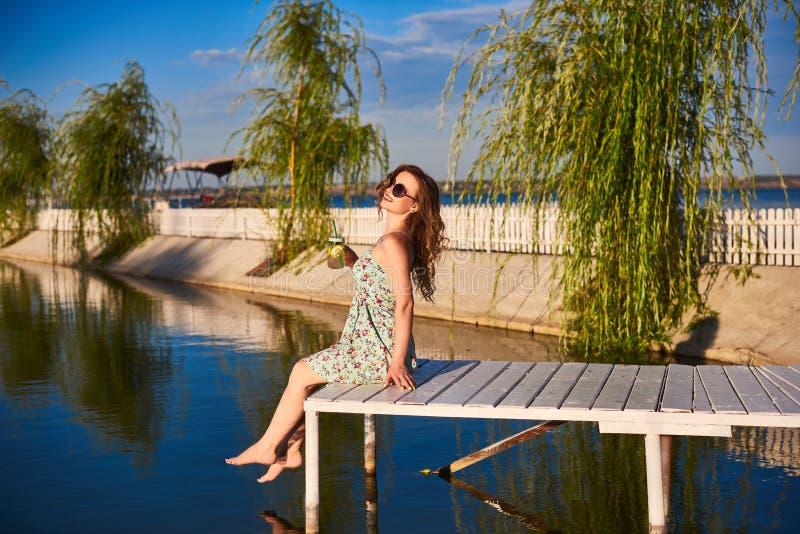 Fille s'asseyant sur le dock en bois au-dessus de l'eau avec mes yeux fermés et appréciant le jour ensoleillé d'été chaud, vue de image libre de droits