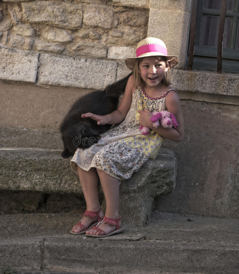 Fille s'asseyant sur le siège en pierre photos stock