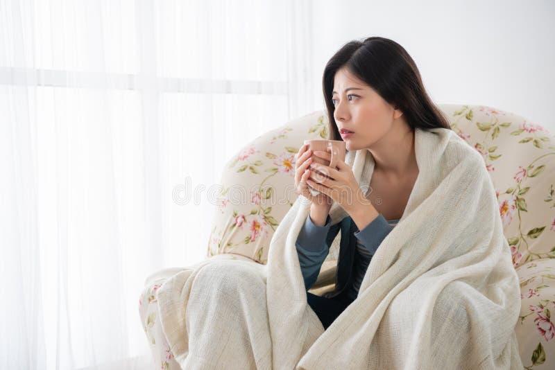 Fille s'asseyant sur le sofa tenant une tasse de café photographie stock libre de droits