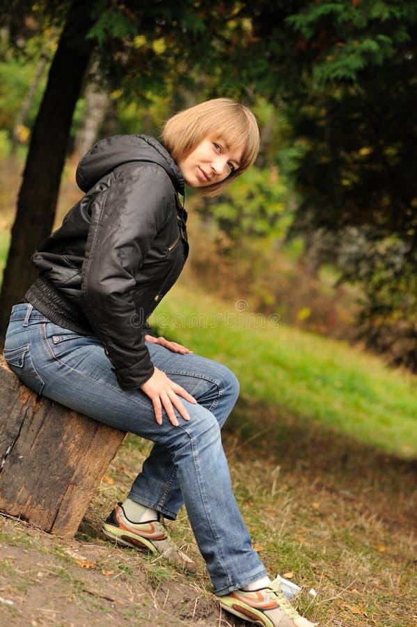Fille s'asseyant sur le tronçon photos stock