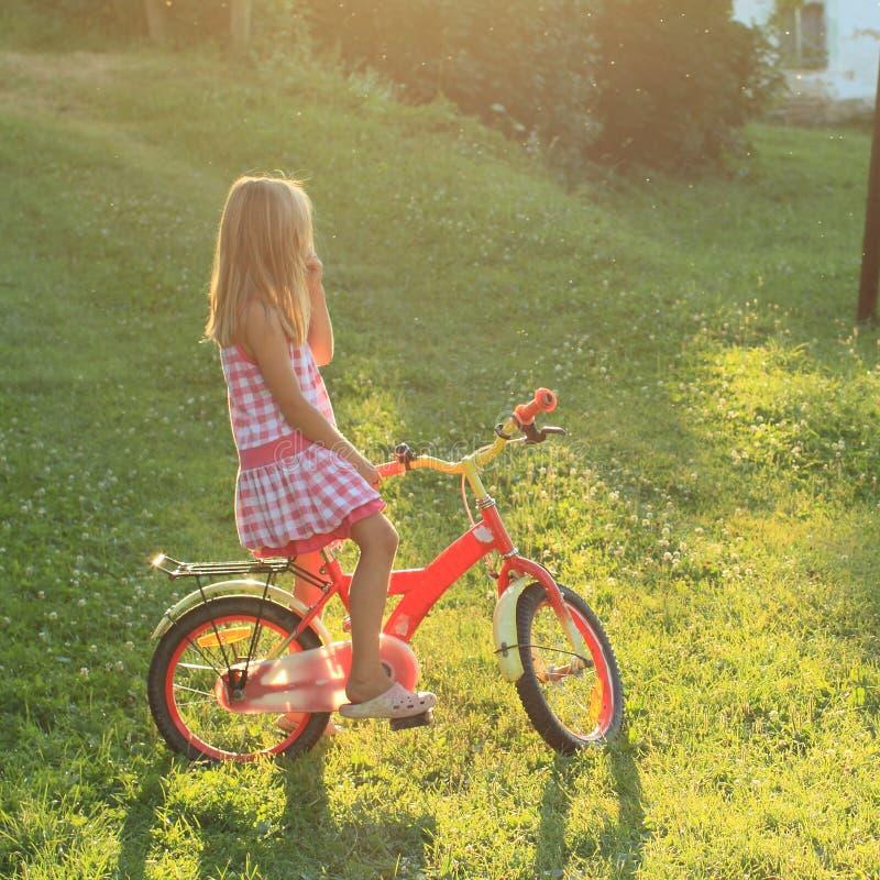 Fille s'asseyant sur un vélo en soleil photographie stock libre de droits