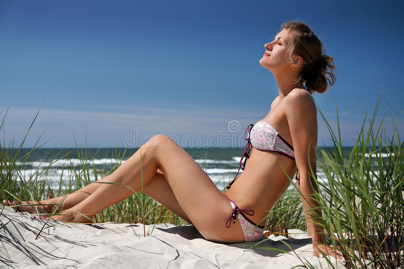 Fille s'asseyant sur une dune photographie stock