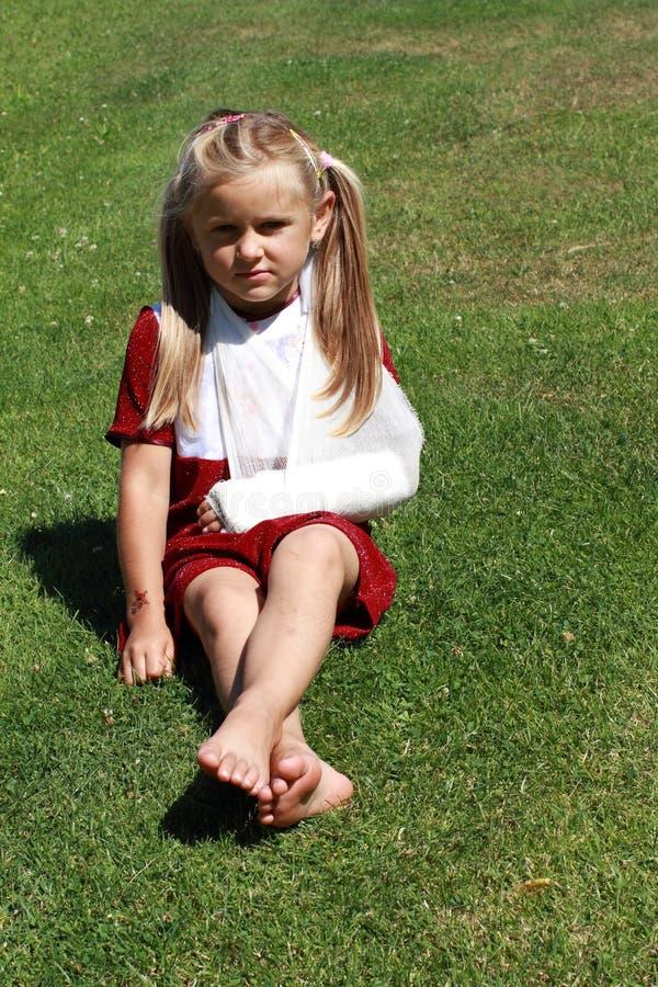 Fille s'asseyante avec la main cassée image stock