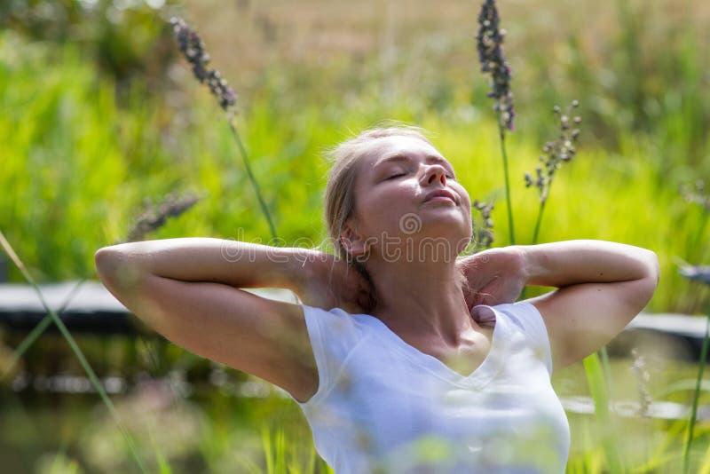 fille 20s blonde appréciant le soleil et le temps gratuit près de l'eau image stock